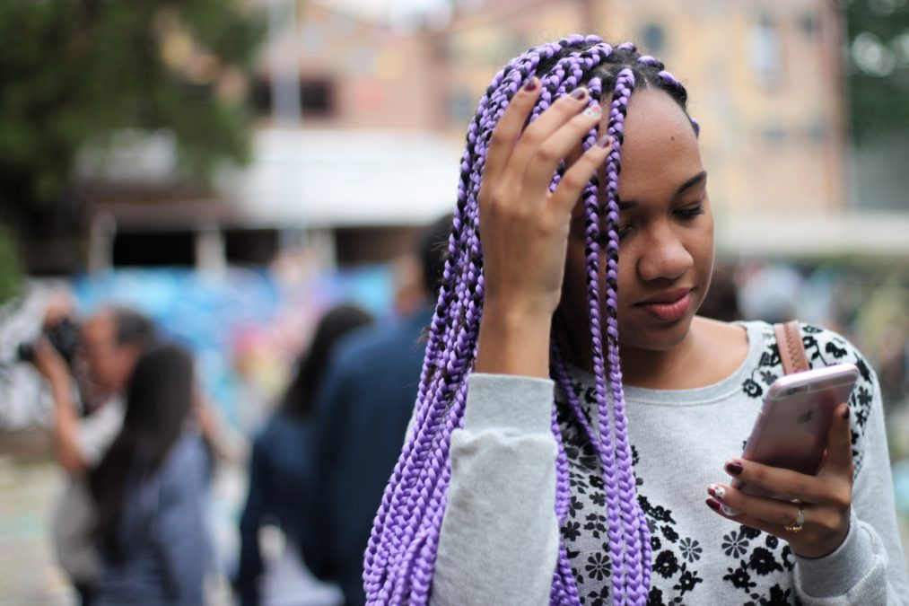 A young black woman with cool purple braids checks her phone. Smartphones can be used for Covid-19 contact tracing.